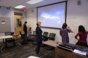instructor watches students write on whiteboard wall