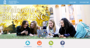 Sakai welcome header of 4 happy students lying on grass in the Quad with a laptop and Sakaiger mascot in hand