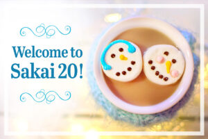 Welcome to Sakai 20 announcement next to cup of hot chocolate with snowman marshmallows