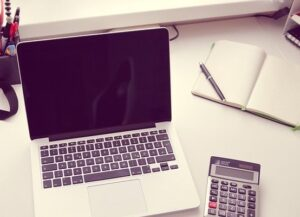 laptop calculator and open notebook on desk
